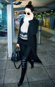 Kendall Jenner wears a fur sweater, long coat, leggings, thigh-high boots, Givenchy bag, and Ahlem sunglasses