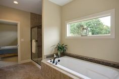 Relax and unwind in a 6ft soaking tub with a small window for privacy and added natural light. This master suite is your own private retreat.