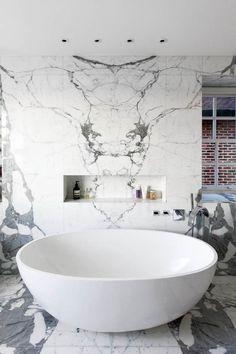 Minimalistic styled bathroom with marble and bowl shaped bathtub
