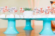 prato de doces azuis com brigadeiros decorados com tags de raposa e guaxinim.