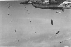 B-24J Liberators of the 579th Bomb Squadron drop incendiary bombs made from fighter plane drop tanks filled with napalm on targets near Royan, France, Apr 15 1945. Note the smoke marker dropped by the lead aircraft. (US National Archives)