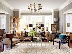 In the Kansas City, Missouri, living room of Hallmark Cards executive David Jimenez, a vintage flokati softens the wood floor. The latticework chair is a 1940s Lorin Jackson design.