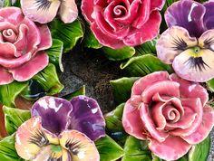 Detail van krans met rozen en violen van keramiek. Deze bloemen liggen op een begraafplaats in Zuid Frankrijk. Detail of a wreath decorated withe roses and violettes. These flowers can be found on a Cemetery in Southern France (July 2013)