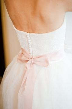 pink bow and back buttons Image by Oh La La Photography via Whimsical Wonderland Weddings