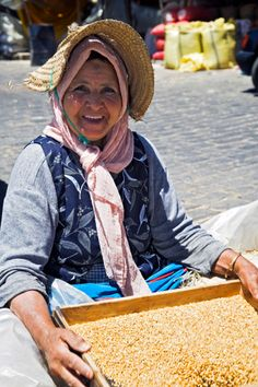 Morocco, Casablanca. A Moroccan woman separates the wheat from the husks using a sieve in the grain market of the Quartier Habous or 'New Medina'.