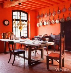 In a restored 18th-century Normandy château, designer Andrew Allfree outfitted the kitchen with a mix of antiques from different periods. Utilitarian objects—like the château's Aga range and original copper pots—play a starring role, as do rich terra-cotta-color walls.DESIGNED BY ANDREW ALLFREE   - Veranda.com