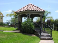 Hexagonal stucco gazebo with Spanish tile roof, decorative wrought iron railing, and acid stained concrete designed and built in the Sugar Land, Texas area.