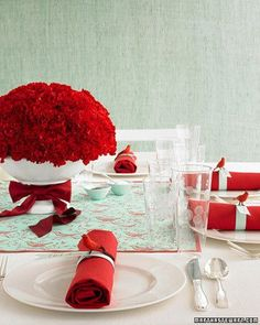 Bold notes, such as a carnation centerpiece or red napkins, pop against white table linens and plates. A hint of aqua adds a surprise to your holiday table.
