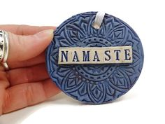 Listing is for one ceramic Namaste ornament. Each ornament hand sculpted, stamped and glazed by me. Measures 3, has a satin ribbon and comes in