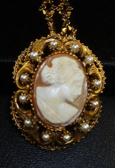 "Offered to you is this beautiful vintage carved shell cameo necklace signed Florenza . The Victorian style pendant features 13 prong set faux pearls in a high relief gold swirl setting. The pendant is just under 1 3/4"" x 1 1/4 and the vintage cameo is 1"" x 1/2"". What makes this special is I added a beautiful double link vintage Trifari neckalce that measures 22"".     Comes in a free hand decorated beautiful shiny black gift box ."