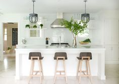 Lush green plants punctuate an all-white kitchen with a glossy island countertop situated in front of  three wooden bar stools.