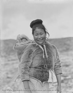 Greenlandic woman with her child in the amaut; anorak with extended hood to carry the baby in