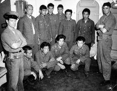 A bord d'un navire deux soldats américains  (U.S. Marine Corps) de chaque côté d'un groupe de prisonniers de la Wehrmacht d'origine asiatique. Trois portent l'insigne l'aigle allemand: très certainement des anciens prisonniers soviétiques recrutés par les Allemands comme troupes auxiliaires: Osttruppen ou Hiwis.