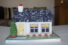 This is back of the house cake I made for one of my good friends when she moved many miles away. This pic was taken before the pastillage picket fence was added, so it's easier to see the detail. It is a little madeira cottage, with individual sugar paste grey roof slates. The walls are 'rendered' in white royal icing; the green bush is royal icing with a terra cotta sugar paste pot; the orange flowers are buttercream; the garden slabs and yellow door are sugar paste; the stones are…