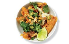 This dish of shatteringly crisp chicken skins tossed with peanuts, chiles, and lime is a riff on Chinese salt-and-pepper squid.