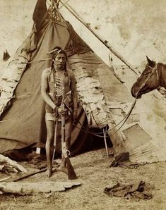 1888 photo of a Blackfeet/Blackfoot Indian warrior photographed in front of his tipi.