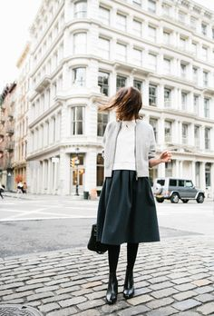 Grey zip front cardigan, white skirt, emerald midi skirt, black tights and black ankle boots.