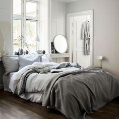 Une chambre aux tons neutres avec un linge de lit dans un camaïeu de blancs et gris et des accessoires déco dans les mêmes tons.