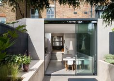 Stainless steel surfaces and a polished concrete floor brighten the interior of this extension to a terraced house in Islington by Architecture for London.
