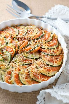 Parmesan Zucchini and Tomato Gratin - Thinly sliced zucchini and tomatoes, layered and baked with onion & garlic and topped with shredded parmesan. This is such a light and delicious side dish.