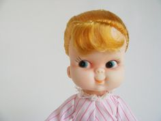 Vintage Plastic and Vinyl Doll. She's a cutie! Strawberry blonde hair in a ponytail with ribbon, pink & white candy striped dress that snaps at the back, white panties, white, removable shoes, arms, legs, & head move, super cute pug nose & shifted eyes.