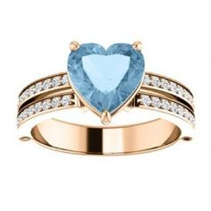 Heart Sky Blue Topaz & Diamond Engagement Ring - An elegant Heart Sky Blue Topaz & Diamond Engagement Ring that features a Sky Blue Heart Shaped stone in a prong setting. It's flanked with 47 White Round accent stones around the shank. The center stone is a Sky Blue Topaz in color, the accent stones are in white with an SI2 in clarity & it's stamped in 18k Rose Gold. The total gem weight of the ring is 2.30 carats & all of the diamonds are 100% natural. #unusualengagementrings