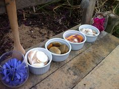 This morning's play invitation in the mud kitchen - 3 kinds of shells, stones, blue and pink flowers.