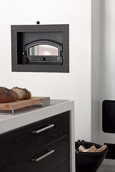 KODIN SYDÄN. Varaava Tiilerin Tyyne-leivinuunitakka rajaa keittiön ja olohuoneen. Se pysyy lämpimänä pitkään ja uunin hiilloksen voi pudottaa leivinuunin alla olevaan takkaan, joka aukeaa olohuoneeseen. | Tyylikäs musta tuo keittiöön luksuksen tuntua | Koti ja keittiö
