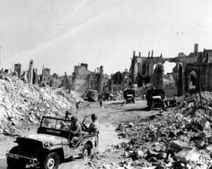 View of the town of Valognes, France, devastated by Allied bombing during the Cherbourg battle, 24 Jun note jeep 'Always Ruth' in foreground. (US National Archives) Jeep Willys, Mind Blowing Images, Normandy Beach, Normandy Ww2, Military Jeep, Military Uniforms, Military Vehicles, Canadian Soldiers, D Day Landings