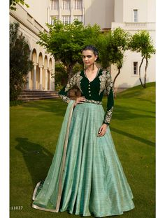 Nakkashi Euphoria 11037. Bottle Green Micro Velvet Top With Stylish V-Neck In Chinese Collar Added With Heavy Embroidered Work. Skirt In Green Khadi. Pallu In Green Net Embellished With Jarkan Work.