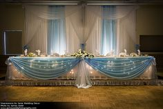 One of our favorites. A pipe and drape backdrop with uplighting and swags, with matching table skirting and coverings.