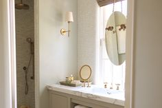 pure and clean. white mosaic tiles, mirror hung with a rope and brass fixtures.
