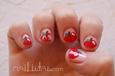 Uñas decoradas con manzanas rojas sobre un color nude y joyas de nail art