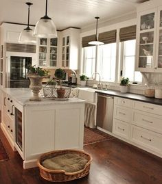 White Kitchen With Dark Countertops And Glass Cabinet Doors Marble Countertop On Island Beadboard Ceiling Wood Floors