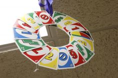 Take a large sturdy paper plate, and fold it in half. Cut out the inner circle, leaving the outer ring to form your wreath shape. Knot a ribbon around the top, then tie it into a bow. Lay the plate flat on a table, and use hot glue to attach UNO cards to the plate to form the wreath. I tried to match up the top left corner of each card to the top right corner of the previous card, slanting each one at a slight angle.