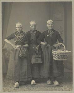 Drie vrouwen, gekleed in de streekdracht van de Noordwest-Veluwe. Over de gedessineerde ondermuts dragen ze een oorijzer met 'krullen ' aan de uiteinden, zichtbaar op ooghoogte. De vrouwen dragen een hemdrok (soort jak) met daarover een kraplap en een schouderdoek. De twee rechter vrouwen dragen daarover nog een jak, wat middenvoor sluit met een grote strik. Verder dragen zij rok, schort en klompen. #Veluwe #Gelderland #oudedracht