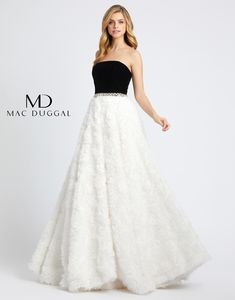 Black and white is an iconic look and when you add a modern trendy twist you get a stunning prom ball gown. Strapless black velvet bodice, rhinestone and clear beaded belt. The full ball gown skirt consists of layers of tulle and net with a finishing layer of white rosettes.