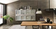 Il segreto di questo ambiente è racchiuso in un mix di pezzi preziosi come il grande tavolo in finitura legno invecchiato e mobili in stile industriale come la madia con le vetrine, come le sedie in stile casa di famiglia.