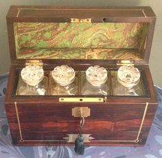 "Regency Period Perfume Bottle Box, made from Brazilian Rosewood, brass inlaid with the typical Regency flush handles to the top and front. The Box has a working lock and key, when open reveals four separated sections containing four cut glass bottles. The box also has a draw with three compartments which is accessed to the front of the box using the flush handle, it is locked using a pin.The interior has been re-lined with a hand marbled paper. 10"" wide x 3.75"" Deep x 7"" tall while closed."