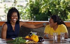 Sharing a laugh: Mrs Obama talks with a young woman at MAiO farm, showing off her toned arms
