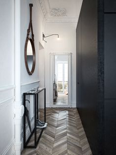 The eye is drawn to the detailed chevron pattern of the timber flooring, then to the slightly detailed lines of the white wall and ceiling, before completing a visual circle by arriving on the plain black wall and fine lines of the black rimmed hall console and mirror opposite.