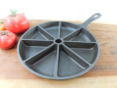 """A cast iron sectional cornbread skillet... Lodge USA... model D28CB... size 9"""" diameter... weight 5.25 lbs... 8 pie shaped sections... Very Good used condition... no cracks or damage... this era pan h"""