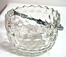 This is an ice bucket with a chrome swing handle in the American pattern made by Fostoria. It measures 6 inches wide by 4.5 inches tall and is in nice condition with no chips or cracks.