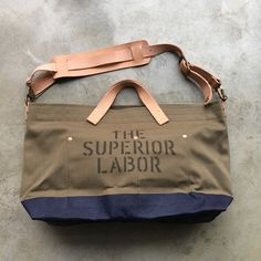 """Sometimes size matters.. If you tend to use an Engineer Bag for travel, the S version may be feeling a bit small for 3+day trips. This stunning L version in khaki/olive drab, navy blue paint and """"military"""" stencil can cope with your kit. Get yours here: https://www.nomadostore.com/collections/the-superior-labor-bags-accessories/products/tsl-engineer-shoulder-bag-l-khaki-body-navy  #thesuperiorlabor #madeinjapan #ruggedstyle #heritage #totebag #bag #nomadostore #napvillage #handmade…"""
