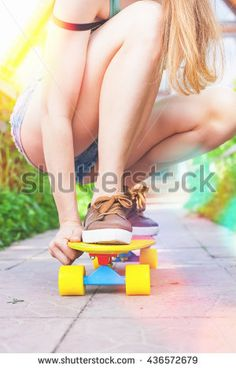 Close-up skateboarder girl riding by skateboard outdoor. Skatebord at city, street. Shoes, stylish sneakers. Skate wheels. Size. Speedy longboard. Cool, Fun Teenager. Skateboarding at Summer