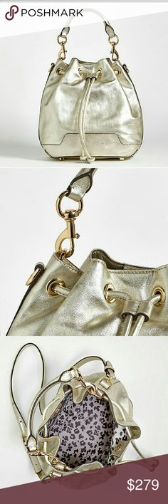 RebeccaMinkoff Gold Leather Convertible Bucket Bag Shimmering gold leather creates an eye-catching look on this chic bucket bag from Rebecca Minkoff. Luxe gold-tone hardware takes the casual silhouette up a notch while the drawstring top offers easy access to your essentials. A truly versatile bag, the rolled-leather carry handle is removable for the days you prefer to use the leather crossbody strap. Elegantly finished with engraved logo plaque in back. Everyday women and celebrities alike…