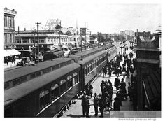 "Union Pacific Train in Long Beach, CA, Circa 1920. A three-car passenger train is shown in the foreground.  Visible businesses at left in the background include Long Beach Drug Company, Hartsook, and Hotel Del Mar.  A streetcar marked ""San Pedro"" is also visible.  At upper right in the background, the Cliff Dwellers' Inn can be seen in the distance. For information about copyright and ordering images from the LBPL Digital Archive, see http://www.lbpl.org/history."