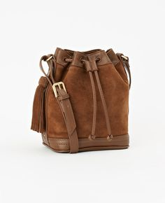 """Rendered in luxe suede, this softly structured bag easily stows essentials with a cinched drawstring design. Drawstring top closure. 52"""" shoulder strap with adjustable notch closure. Side zipper with tassel. Fabric lined interior."""