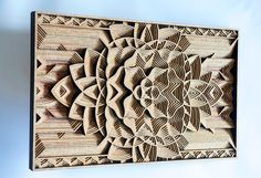 """Working with precisely cut 1/8"""" pieces of laser-cut mahogany plywood, Oakland-based artist Gabriel Schama creates densely layered wood relief sculptures that twist, intersect, and overlap to create various mandala-like forms. Each piece begins as a vector illustration which is fed into his laser cut"""