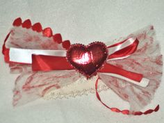 White tulle printed with red hearts, red and white ribbon with red hearts and a glittered red heart.  Cream lace headband.  6 in. wide 3 in. long.  Fits Infant